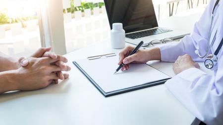 De vrouwelijke zilveren pen van de artsenhand vullende geduldige geschiedenislijst bij klembordstootkussen Stockfoto
