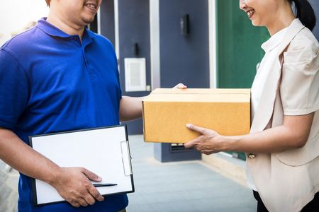 Postal - delivery of a package through a  service; Woman customer hand accepting receipt cardboard box while young deliveryman holding clipboard. Stock Photo