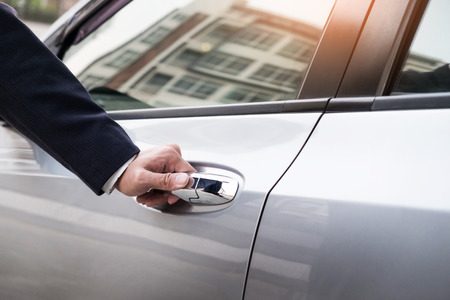 Chauffeur s hand on handle. Close-up of man in formal wear opening a passenger car door. Stockfoto