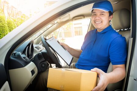 Delivery man with cardboard box checking document list In van and parcels on seat outside the warehouse. Stock Photo