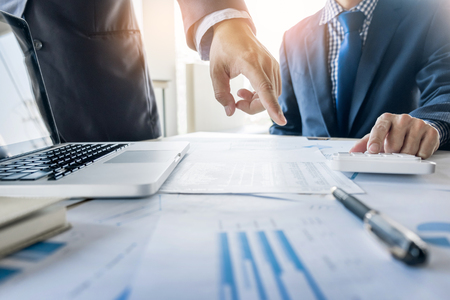 Administrator business man financial inspector and secretary making report, calculating or checking balance. Internal Revenue Service inspector checking document. Audit concept.
