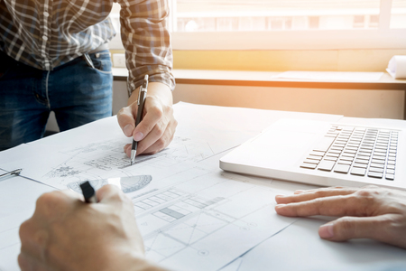 architect: Architects engineer discussing at the table with blueprint - Closeup on hands and project print, Team group on construciton site check documents and business workflow.
