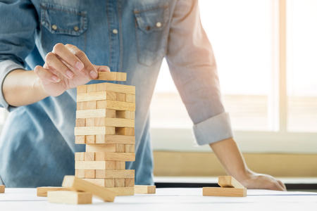 Hand of engineer playing a blocks wood tower game (jenga) on blueprint or architectural project