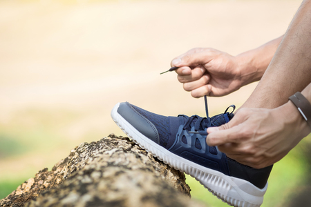 Cropped shot of young man runner tightening running shoe laces, getting ready for jogging exercise outdoors. Male jogger lacing his sneakers standing on forest path before morning run.
