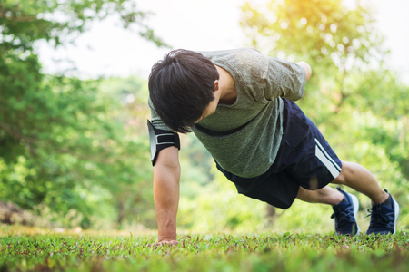 hand push-up. Confident muscled young man wearing sport wear and doing hand push-up while exercising on outdoor park.