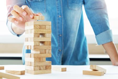 積み木する木製タワー ゲーム (ジェンガ) 青写真または建築プロジェクトにエンジニアの手 写真素材