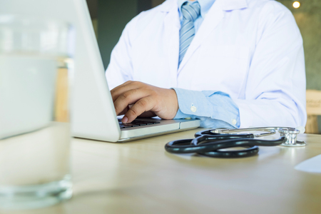 Close up of unknown male doctor sitting at the table near the window in hospital and typing at laptop computer..