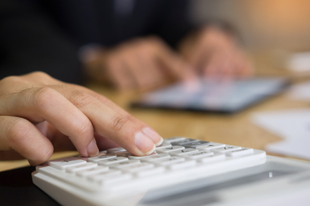 business man financial inspector and secretary making report, calculating or checking balance. Internal Revenue Service inspector checking document. Audit concept at working with plan on office desk and modern digital tablet