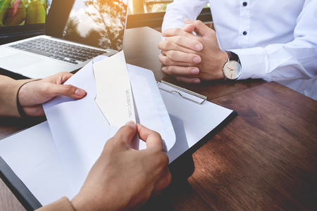Hand of a businessman hands over a resignation letter on a wooden table to his boss. Stock Photo - 82508019