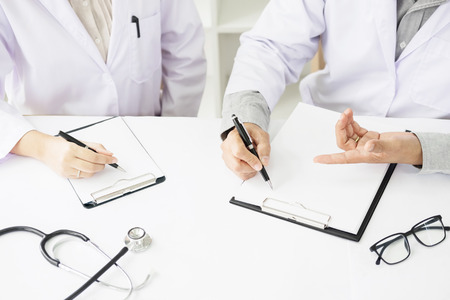 Two doctors discussing patient notes in an office pointing to a clipboard with paperwork as they make a diagnosis or decide on treatment.