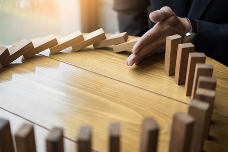 interrupt: businessman hand stop dominoes continuous toppled or risk with copyspace
