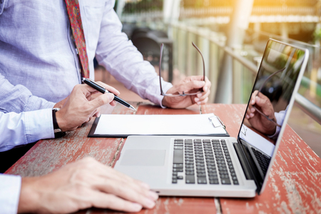 Two businessmen discussing planing tasks with laptop computer sitting at outdoor table.