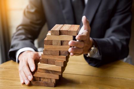 ビジネス コンセプト、実業家、塔に木製のブロックを配置することをギャンブル保険リスクと富の戦略を計画します。