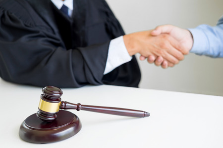 Gavel Justice hammer on wooden table with judge and client shaking hands after adviced in background at courtroom, lawyer service concept Reklamní fotografie