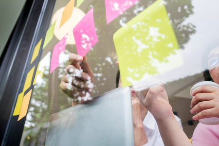 business man sticking adhesive notes on glass wall in office and discussting with team.
