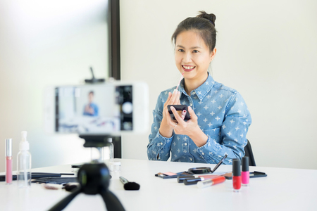 woman present beauty cosmetic product and broadcast live video to social network by internet at home, beauty blogger concept Stockfoto