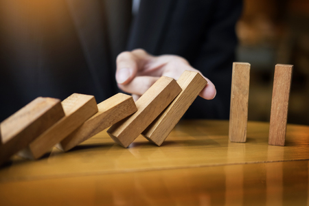 businessman hand stop dominoes continuous toppled or risk with copyspace Stock Photo - 86872399