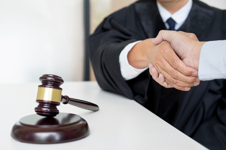 judicial proceeding: Gavel Justice hammer on wooden table with judge and client shaking hands after adviced in background at courtroom, lawyer service concept Stock Photo