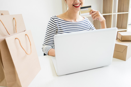 Closeup of happy young woman holding credit card inputting card information while and using laptop computer at home. Online shopping concept