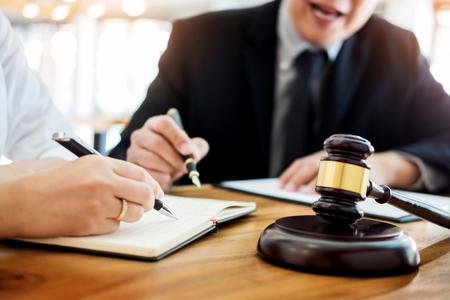 Los hombres de negocios y los abogados que discuten los papeles del contrato que se sientan en la tabla. Conceptos de derecho, asesoramiento, servicios jurídicos.
