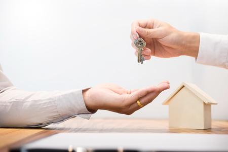 Agente immobiliare vestito seduto in una scrivania Consegna delle chiavi di casa con il cliente dopo la firma del contratto.