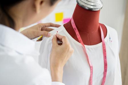 Le tailleur asiatique ajuste le design du vêtement sur le mannequin dans l'atelier. Ajuste un peu son travail sur le modèle en studio.