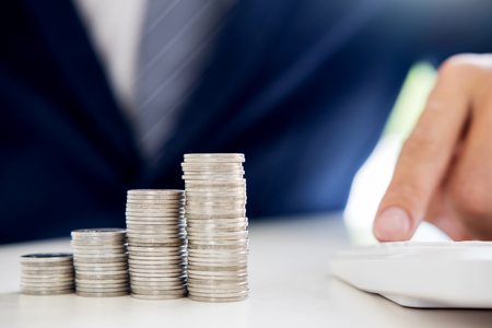 Business man putting coin to rising pile of money and calculator, Saving money investment and financial concept