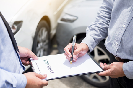 Car insurance agent send a pen to his customers sign the insurance form on clipboard while examining car after accident claim.