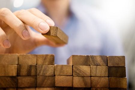 Hand of engineer playing a blocks wood tower game on blueprint or architectural project concept Stock Photo