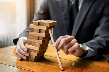Planning, risk and wealth strategy in business concept, businessman and insurance gambling placing wooden block on a tower.