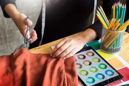 Hands notch tailor tailor's scissors cloth cutting a piece of fabric (fashion designer concept) Standard-Bild