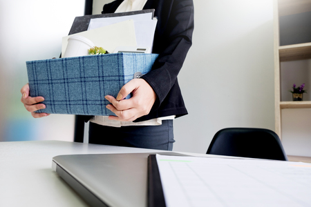 business woman packing personal company belongings when she deciding resignation and changing work in future. Фото со стока