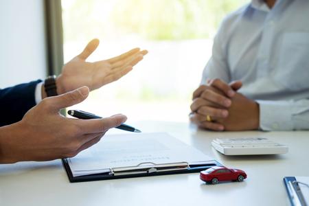 transport en eigendom concept - klant en verkoper met autosleutel Stockfoto