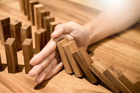 Businessman's hand stop dominoes continuous toppled or risk with copyspace