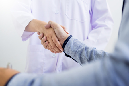 Doctor shakes hands at medical office with patient, wearing glasses, stethoscope and lab coat Stock Photo