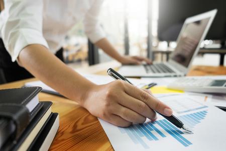 ノートパソコンの紙、鉛筆、オフィスで手をつないで木製の机(テーブル)で働くビジネスマン、金融概念 写真素材