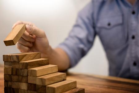 De bedrijfsmensenhand zette houten blokken die het stapelen voor ontwikkeling schikken als stappentrede, Concept de groei en succesplan.