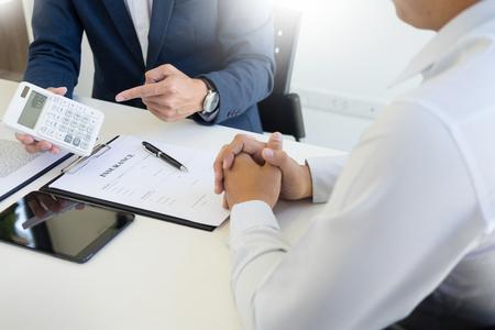 Verkäufer, der einen Schlüssel hält und dem Käufer einen Preis im Autohausbüro für Autoversicherungspreis berechnet Standard-Bild