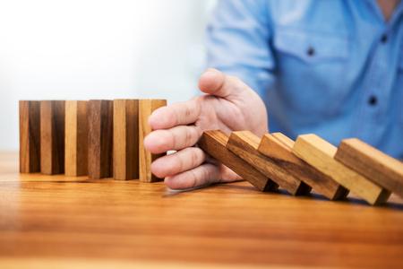Zakenman hand stop domino's continu omvergeworpen of risico met copyspace Stockfoto