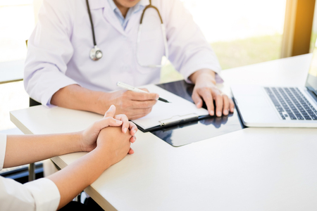 patient listening intently to a male doctor explaining patient symptoms or asking a question as they discuss paperwork together in a consultation Stok Fotoğraf - 94141589