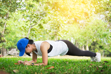 hand push-up. Confident muscled young women wearing sport wear and doing hand push-up while exercising on outdoor park. Stock Photo