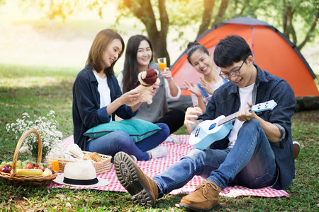 summer, holidays, vacation, music, happy people picnic concept - group of friends with ukulele having fun