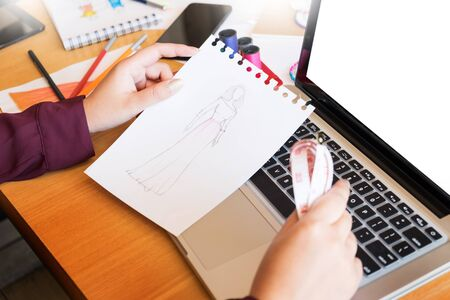 young women working as fashion designer drawing sketches for clothes in atelier paper at workplace studio Stock Photo