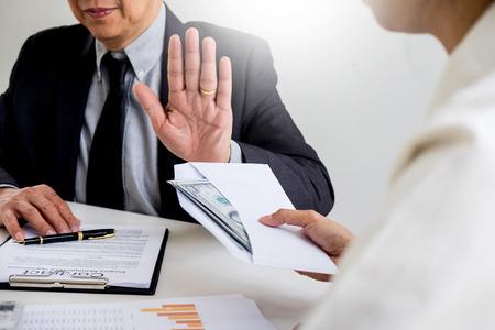 封筒の中でお金を拒否または拒否するビジネスマン - 贈収賄防止と汚職の概念