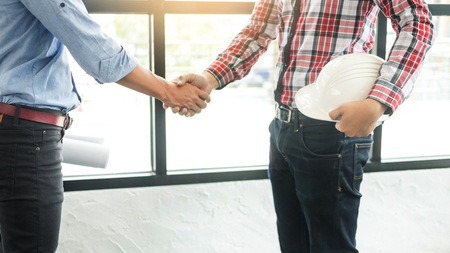 architecture and home renovation concept - builder with blueprint shaking partner hand. 版權商用圖片
