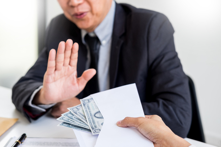 Businessman refusing or rejecting money in the envelope - anti bribery and corruption concepts