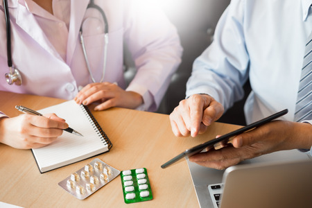 Two doctors discussing patient notes in an office pointing to tablet as they make a diagnosis or decide on treatment. Banco de Imagens
