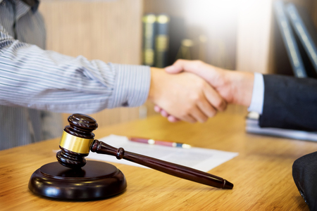 Gavel Justice hammer on wooden table with judge and client shaking hands after adviced in background at courtroom, lawyer service concept Standard-Bild