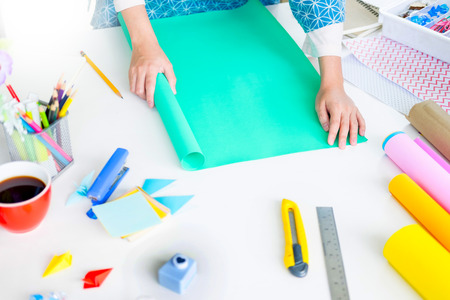 Woman's hand cut paper Making a scrap booking or other festive decorations DIY accessories arrangement