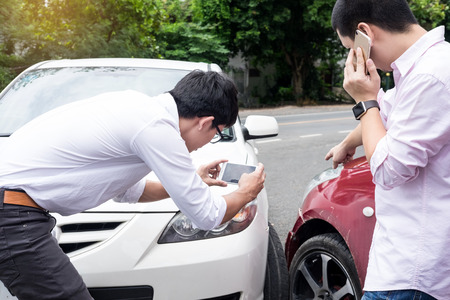 Male Driver take pictures of accident-damaged vehicle with a holding smartphone After Traffic Collision proof of insurance claim.